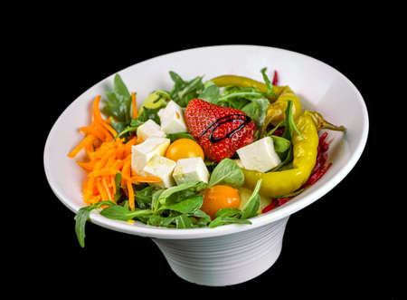 FOOD - Fresh mixed salad with cheese and strawberry, green peppers, jalapeño, arugula. carrot and beet, in a withe stylish dish. Black background.