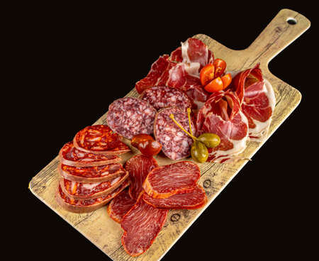 Wooden board with spanish iberian deilcatessen: cured ham, cherry tomatoes, chorizo, salami, capers and sured loin. With text space