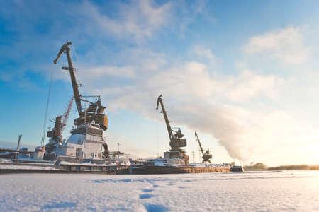 Ships cargo cranes on shore in winter Stock Photo