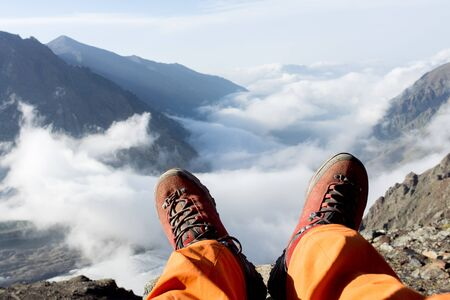 zapatos de seguridad: tired feet of the climber in the shoes on the mountains. Foto de archivo