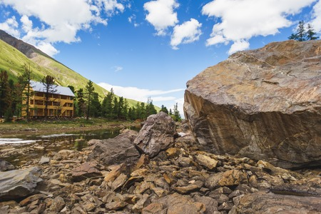 wolfgang: wooden hotel in the mountains near a large rock. Altai