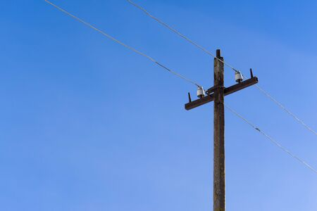 an old pole for wire on blue sky background