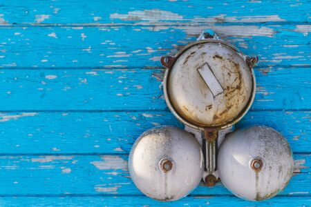 intruder: Classic alarm bell on a blue wooden wall in the winter on the outside. Close up