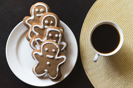 gingerbread man: gingerbread men on a white plate on black background with a cup coffee.