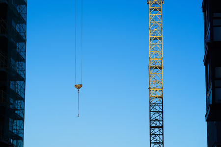 construction crane on the sky background among buildings. Stock Photo