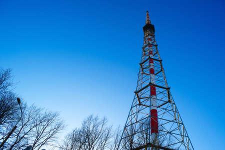 telecommunications tower on blue sky background. sun