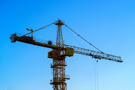 construction crane on the blue sky background. Stock Photo