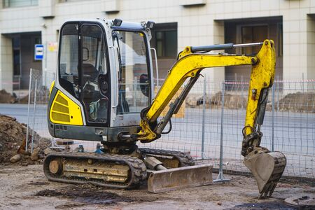 Orange mini excavator on a construction site