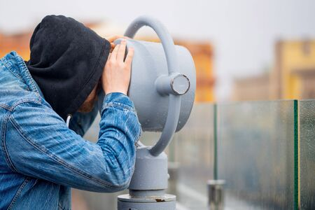 the man looks through his binoculars on the lookout closeup