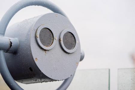 operated: closeup coin operated binoculars overlooking after rain Stock Photo