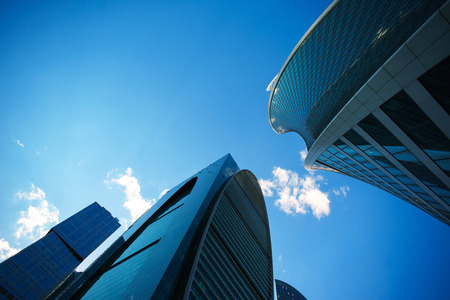 Underside angle view to background of modern glass building skyscrapers over blue sky