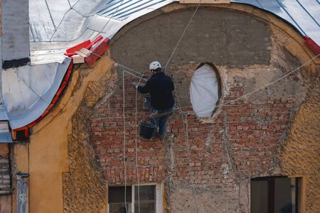 industrial climber restores wall on the building