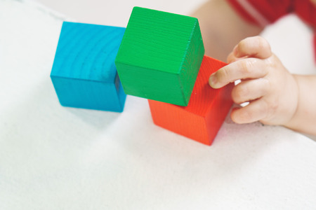 hands baby. the child plays with toys. colored cubes