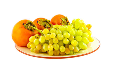 Grapes and persimmons on plate. Isolated on white