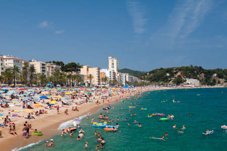 LLORET DE MAR, SPAIN - JULY 8, 2010 - People swim and sunbathe at the city beach of Lloret de Mar - one of the most popular holiday resorts in Spain