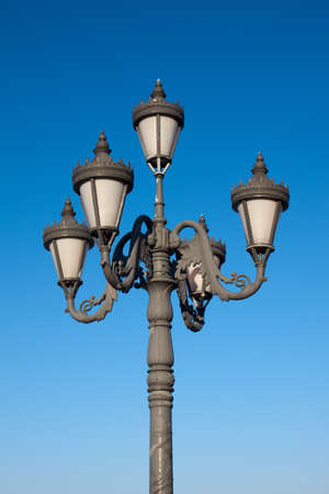 Old fashioned street lamp over blue sky