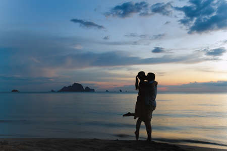 Young couple is kissing at sunset