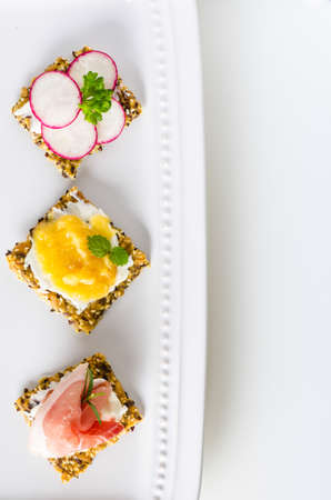 Homemade crisp bread as appetizers with prosciutto, radish and jam photo