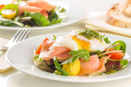 Poached egg salad with smoked salmon, cherry tomatoes and pesto  Stock Photo
