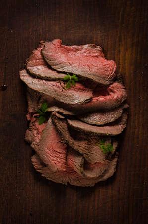Juicy roast beef slices on cutting board