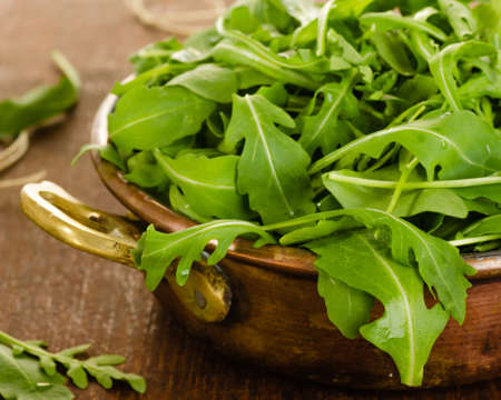 Fresh rucola salad leaves in bowl on wooden background