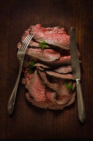 Juicy roastbeef slices on cutting board
