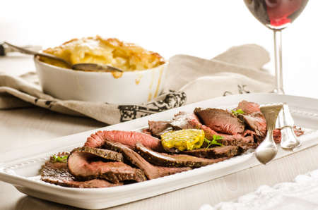 slices of roast beef with potato gratin and red wine on the table