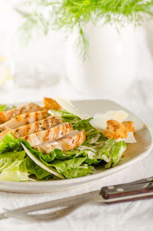 Chicken Caesar salad on the white plate photo