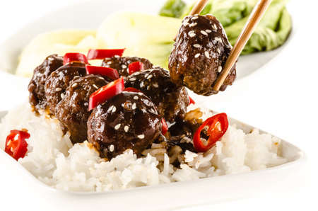 bok choy: Asian meatballs with chinese sauce served with rice, steamed bok choy, sesame seeds and chili