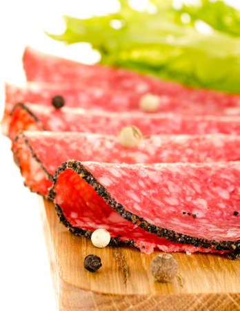salami slices: Salami slices on the cutting board whith salad leaves and peppercorns
