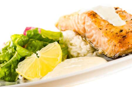 side salad: Salmon steak with rice, creamy sauce and side salad Stock Photo