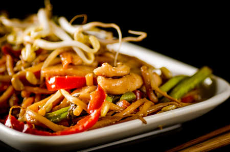 hoisin sauce: Stir-fried chinese noodles with chicken, vegetables and beansprouts on black