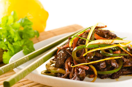 cilantro: Beef, carrots and green bell pepper in asian citrus sauce with chopsticks, bamboo mat, lemon Foto de archivo
