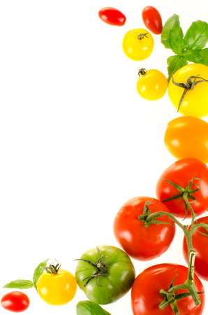 Frame of colorful heirloom tomatoes isolated on white Stock Photo