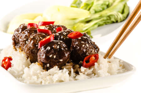 hoisin sauce: Asian meatballs with chinese sauce served with rice, steamed bok choy, sesame seeds and chili