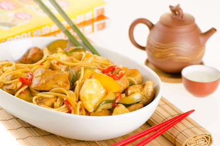 hoisin: Stir-fried noodles with chicken and vegetables served in a bowl, over bamboo mat with tea Stock Photo