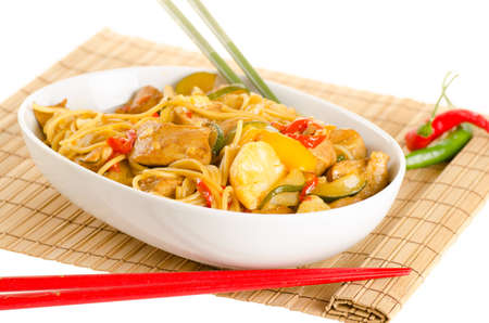 hoisin: Stir-fried noodles with chicken and vegetables served in a bowl, over bamboo mat with chopsticks and chili pepper