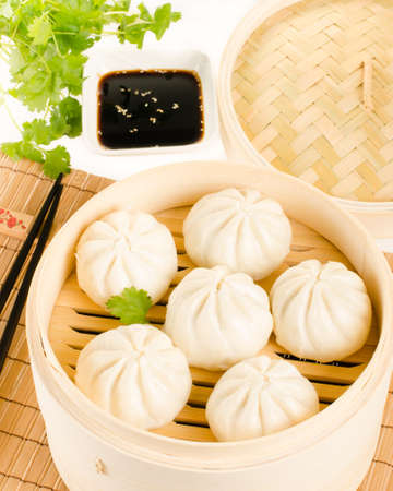 Chinese steamed buns in bamboo steamer basket with cilantro, soy sauce and chopsticks on white