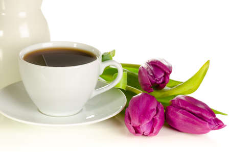 White cup of coffee with bunch of purple tulips on white background