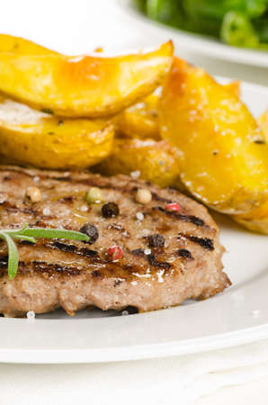 side of beef: Beef burger with the roasted potato, side salad and spices on white Stock Photo
