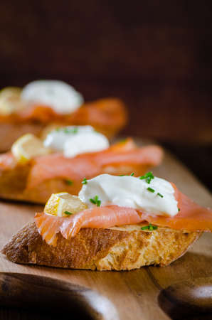 smoked salmon on toasted bread with cream fresh, lemon and chives on wooden background