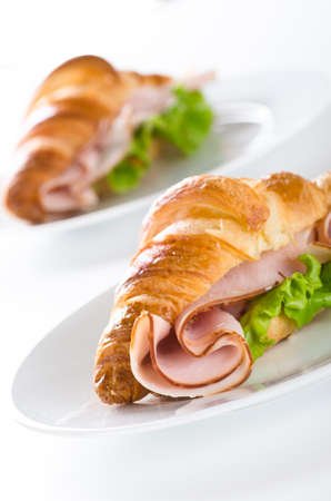 Fresh croissant with ham and salad leaf on white white Banque d'images