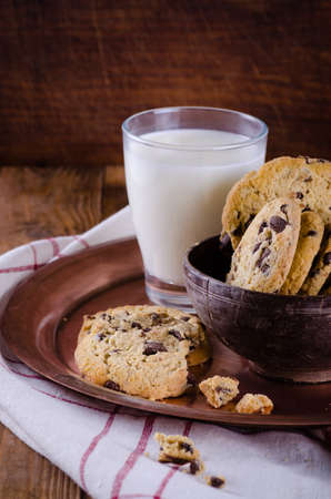 Chocolate chip cookies in a bowl on wooden table with glass of milk