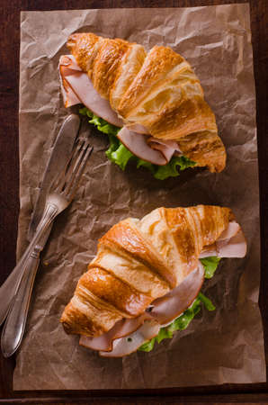 Fresh croissant with ham and salad leaf on baking paper