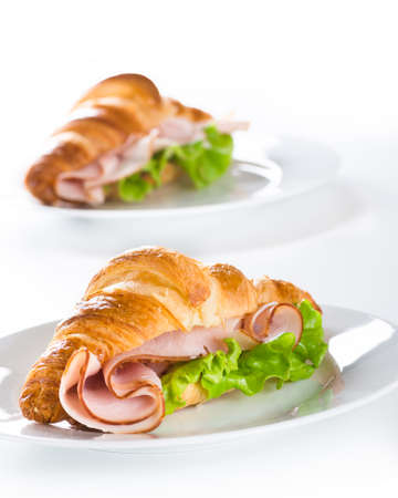 Fresh croissant with ham and salad leaf on white white Stock Photo
