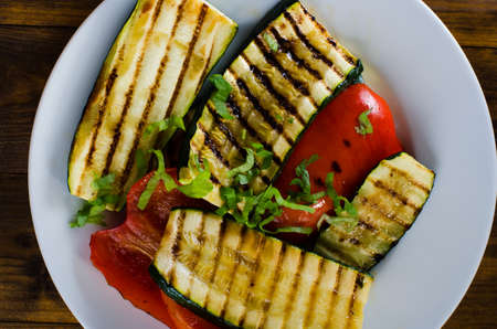 Grilled vegetables on plate on wooden background Stock Photo