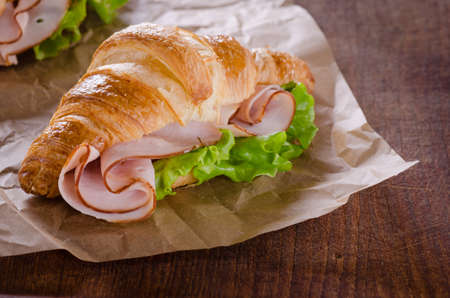 Fresh croissant with ham and salad leaf on dark wooden background Stock Photo