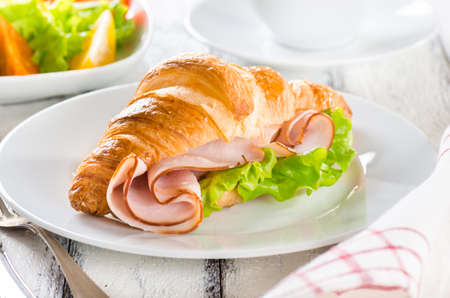 Fresh croissant with ham and salad leaf on white wooden background