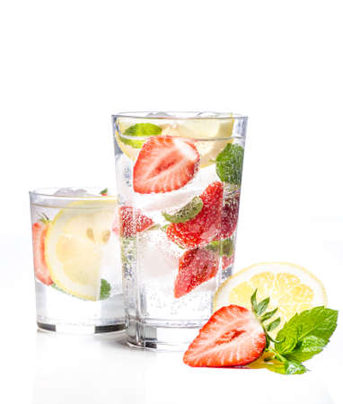 Glass of lemonade with lemon, lime and strawberries on white background