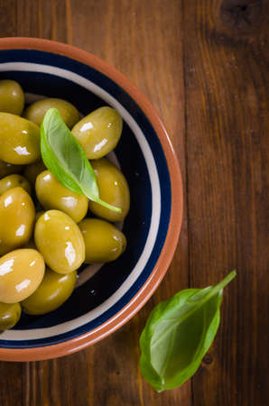Green olives on a wooden plate